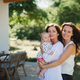 Woman with daughter and baby granddaughter resting outdoors in backyard - PhotoDune Item for Sale