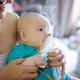 Girl making inhalation with nebulizer while sitting on mom's lap at home - PhotoDune Item for Sale