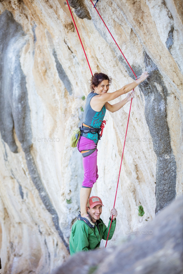 Female rock climber standing on shoulders of her partner - Stock Photo - Images