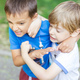 Two boys fighting outdoors. Friends wrestling in summer park. - PhotoDune Item for Sale