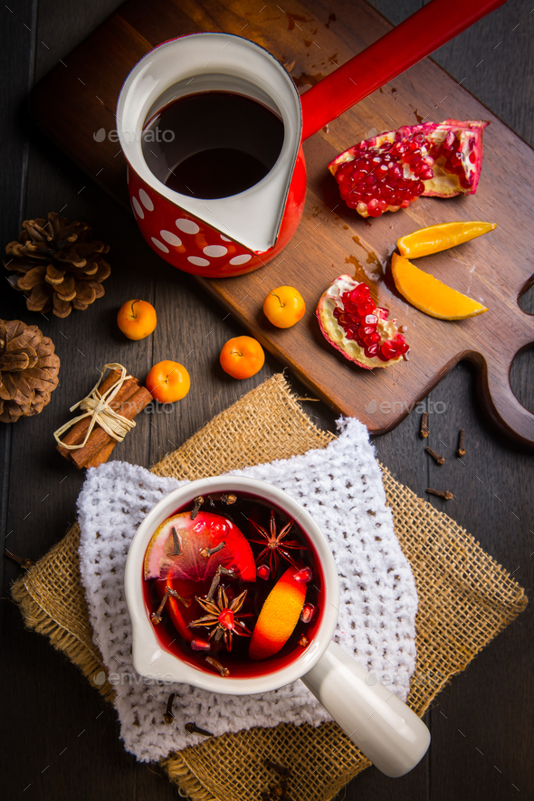 Hot spicy mulled wine with fruits and spices in mug - Stock Photo - Images