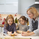 Blond woman wearing blue apron and two girls standing in kitchen, baking Christmas cookies. - PhotoDune Item for Sale