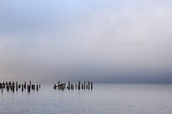 Wooden poles in ocean under cloudy sky - Stock Photo - Images