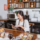beautiful woman smiles wearing an apron while using a tablet - PhotoDune Item for Sale