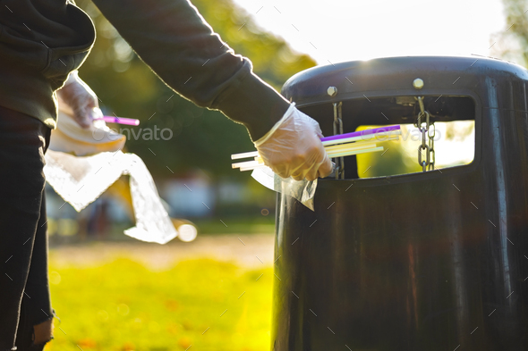 Volunteer putting straws in garbage bin at park - Stock Photo - Images