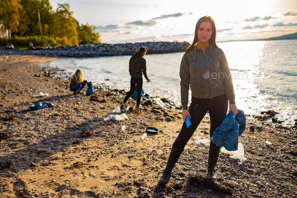 Serious young woman cleaning beach for plastic with volunteers during sunset - Stock Photo - Images
