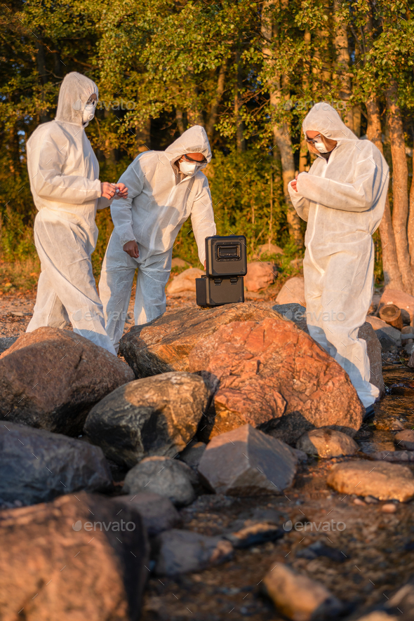 Researchers in team with container at beach taking water samples - Stock Photo - Images