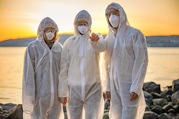 Dedicated team of scientists holding water sample at beach - Stock Photo - Images