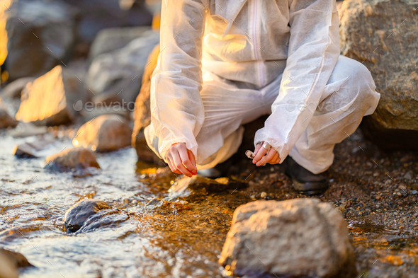 Close-up of researcher collecting water sample at seashore - Stock Photo - Images