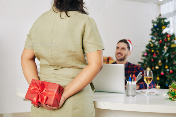 Businesswoman surprising coworker with Christmas present when they are working in office