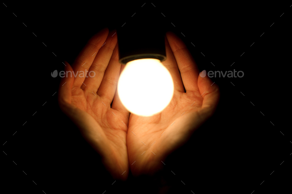 light bulb in humans hands on black background, energy saving and innovation concept - Stock Photo - Images