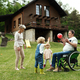 Small children with senior grandparents in wheelchair playing with a ball in garden - PhotoDune Item for Sale