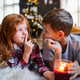 Small girl and boy with candle indoors at home at Christmas, making silence gesture - PhotoDune Item for Sale