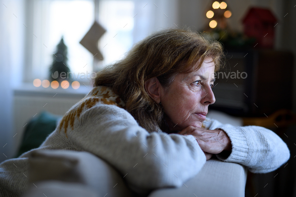 Lonely senior woman sitting on sofa indoors at Christmas, solitude concept.