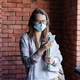 Girl student in a protective medical mask on her face looks at the phone. - PhotoDune Item for Sale