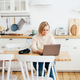 Woman working at home in kitchen wirelessly in laptop. - PhotoDune Item for Sale