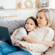 Mom and daughter lie on the couch and hug, look at the laptop screen. - PhotoDune Item for Sale