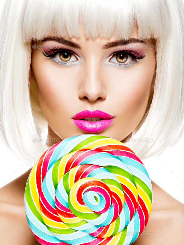 Face of a beautiful  girl with pink make-up and multicolor sweet candy. - Stock Photo - Images