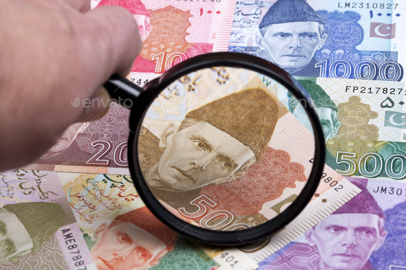 Pakistani rupee in a magnifying glass - Stock Photo - Images