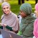 Muslim Lady Recommending Smartphone Mobile Application To Friends Sitting Outdoors - PhotoDune Item for Sale