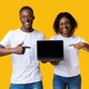 Young black couple pointing at blank laptop screen - PhotoDune Item for Sale