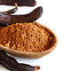Dry carob powder and pods in a wooden bowl close up - PhotoDune Item for Sale