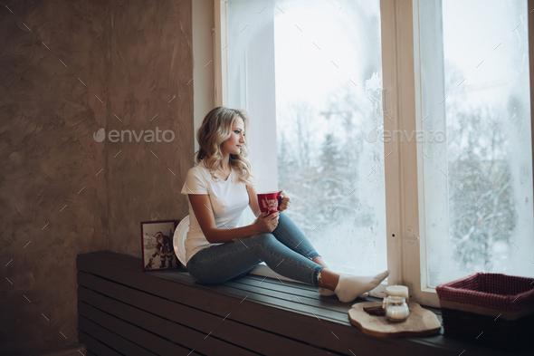 Beautiful blonde sitting on window sill with mug. - Stock Photo - Images