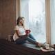 Beautiful blonde sitting on window sill with mug. - PhotoDune Item for Sale
