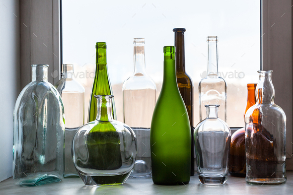 various empty bottles on sill of home window - Stock Photo - Images