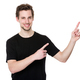 Happy young man pointing to blank space on the right - PhotoDune Item for Sale