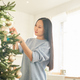 Woman decorating tree for Christmas - PhotoDune Item for Sale