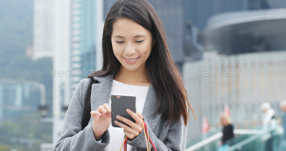Woman use of mobile phone and holding shopping bag - Stock Photo - Images