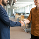 Handshake of two young male colleagues in casualwear standing in the aisle - PhotoDune Item for Sale