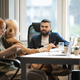 Young bearded businessman with smartphone talking to mature female colleague - PhotoDune Item for Sale