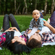 Mother, father and little baby leisures on grass - PhotoDune Item for Sale