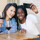 Two friends making a selfie sitting at a table outside a bar while drinking a glass of red wine - PhotoDune Item for Sale