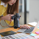 Designers are looking at camera photos and using a laptop. - PhotoDune Item for Sale
