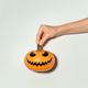 Hand holds halloween pumpkin on white wall - PhotoDune Item for Sale