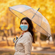 Pretty young woman in surgical mask on walk under rain at park on fall day - PhotoDune Item for Sale