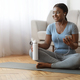 Cheerful black woman resting after home workout with water and smartphone - PhotoDune Item for Sale