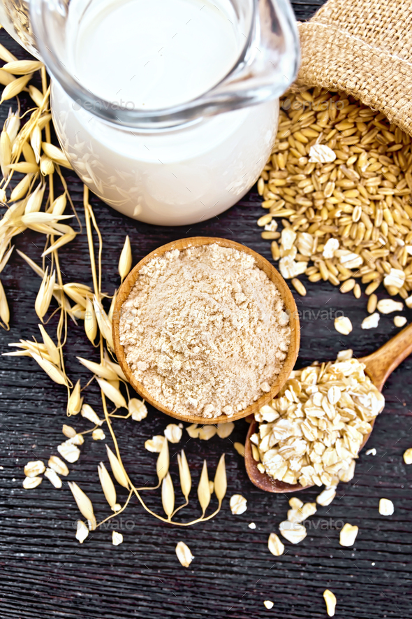 Flour oat in bowl with grain on board top - Stock Photo - Images