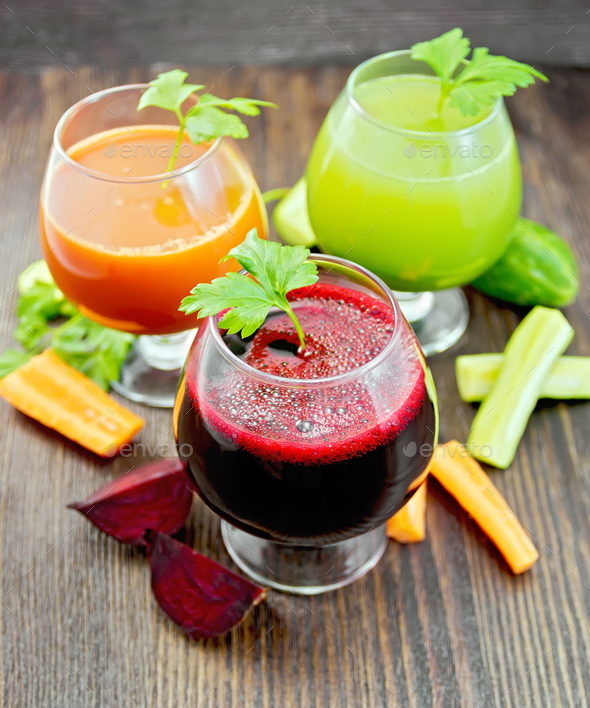 Juice beet and cucumber in wineglass on dark board - Stock Photo - Images