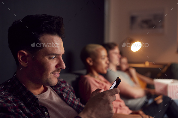 Man Using Mobile Phone Whilst Friends Watch TV At Home In Evening - Stock Photo - Images