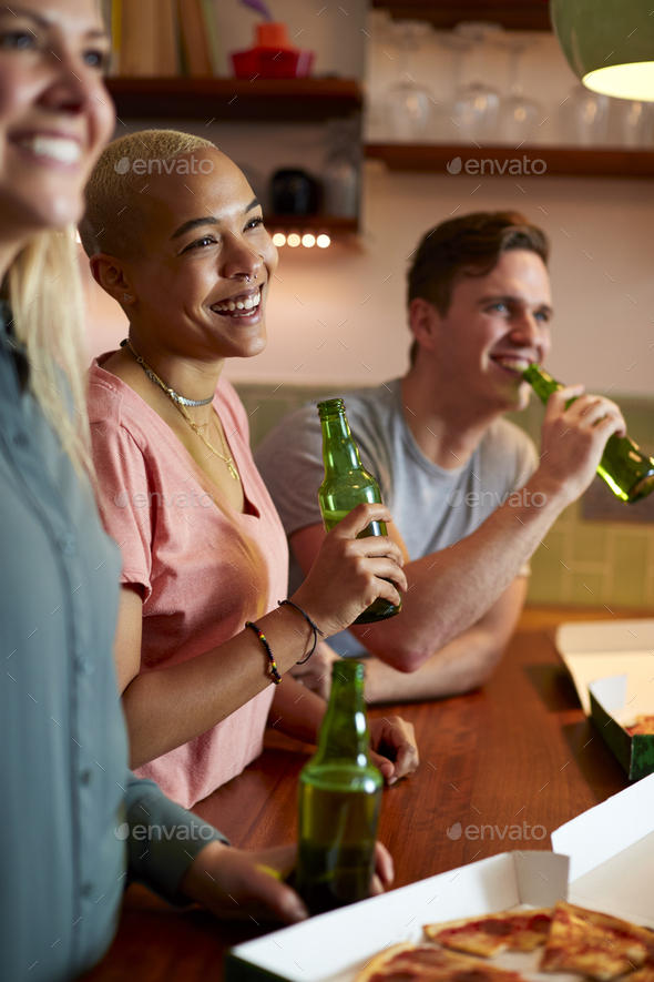 Group Of Friends Celebrating With Beers Meeting At Home And Eating Takeaway Pizza - Stock Photo - Images