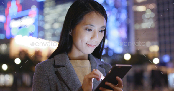 Businesswoman use of mobile phone in city at night - Stock Photo - Images