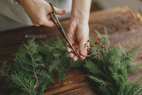 Making rustic christmas wreath, seasonal winter workshop. Florist  holding scissors and berries - Stock Photo - Images