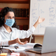 Teacher in mask having video conference chat with students - PhotoDune Item for Sale
