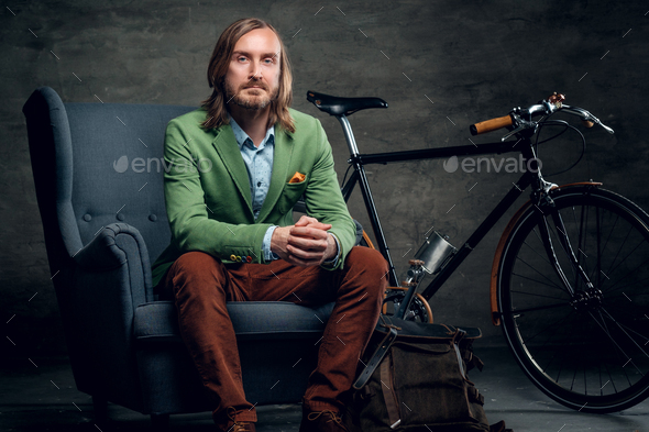 A man sits on a chair with the bike on a background. - Stock Photo - Images