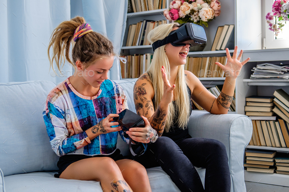 Two females having fun with virtual reality glasses. - Stock Photo - Images