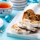 Christmas stollen. Traditional German festive dessert with cup of tea. Blue background. Close up - PhotoDune Item for Sale